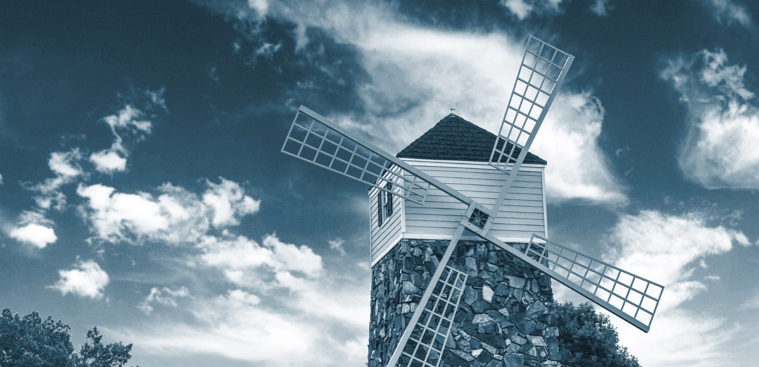 A windmill standing against a peaceful blue sky.